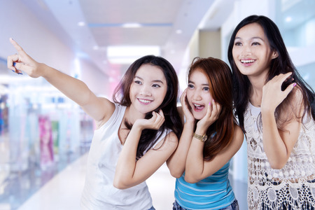 indonesian woman: Portrait of three beautiful teenage girls in the shopping center and looks happy when looking at a shop
