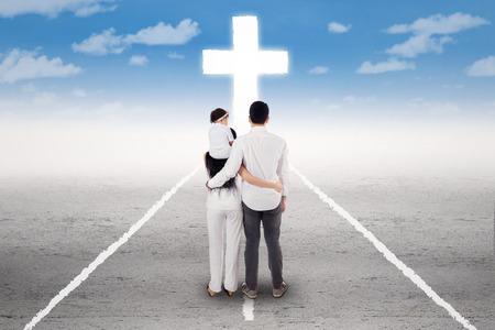 familia cristiana: Vista trasera de la familia de pie en la carretera y seguir una cruz en la final de la carretera