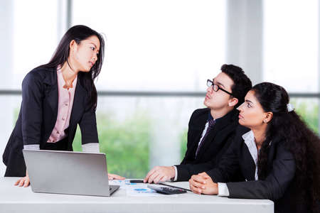 conflict: Portrait of businesswoman looking at her employees seriously with angry expression Stock Photo