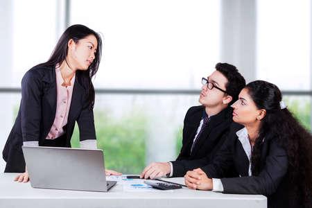 conflict: Retrato de mujer de negocios mirando a sus empleados en serio con la expresión enojada