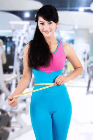 waistline: Attractive female fitness trainer use a measurement tape to measure her waistline at gym center Stock Photo