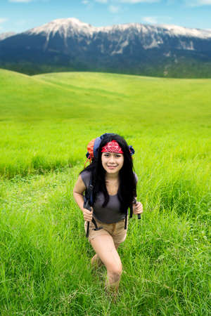 Beautiful woman carrying a rucksack while walking on the mountain and smiling at the camera photo