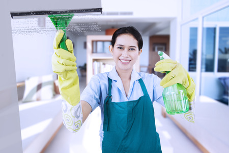 indonesian woman: Portrait of friendly maid wearing uniform and apron, cleaning a mirror with a spray while smiling