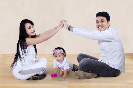 niños sosteniendo un cartel: Joven familia feliz asiática haciendo el signo de casa en casa