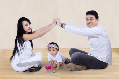 family asia: Young happy asian family making the home sign at home