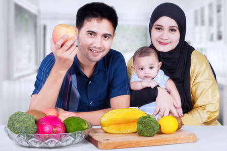 moslem: Portrait of two parents sitting at home with their little son and fresh fruit on the table Stock Photo