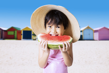 pink bikini: Young asian little girl eating a fresh watermelon on the beach while wearing swimsuit and hat
