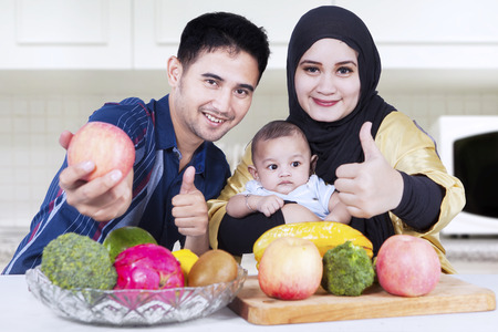 thumbsup: Portrait of cheerful parents with their baby and fresh fruit, showing thumbs-up on the camera, shot in the kitchen Stock Photo