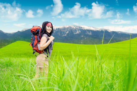 Portrait of pretty female hiker smiling at the camera while carrying a backpack and walking on the mountain photo