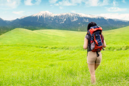 Back view of female hiker walking toward the mountain through the green meadow while carrying a backpack photo