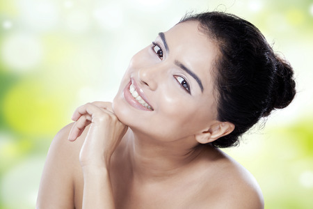 clear skin: Beauty face of young female model with smooth skin after skincare, smiling at the camera on blur background