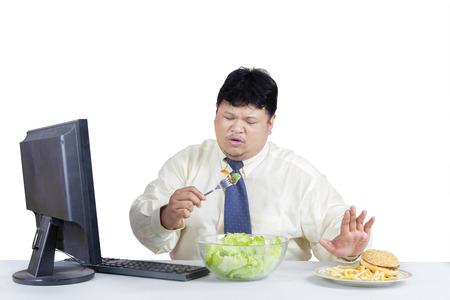 comida chatarra: Empresario sobrepeso evitar la comida chatarra y optar por comer ensalada