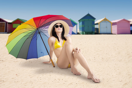 brighton: Beautiful sexy woman wearing swimsuit on the beach, while sitting on the sand under colorful umbrella Stock Photo