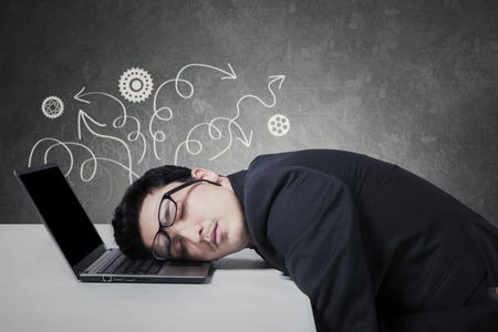 Young male entrepreneur in business suit, sleeping on laptop with stressful expression photo