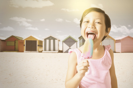 child ice cream: Portrait of pretty little child licks a fresh ice cream on the beach, shot with an instagram filter Stock Photo