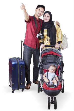 Portrait of two parents going to travelling while carrying their baby on the stroller, isolated on white background