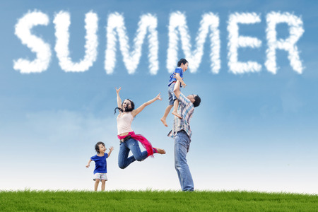 indian summer seasons: Portrait of playful family having fun together on the park with green grass under a summers cloud