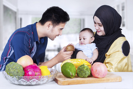 moslem: Portrait of healthy family with fresh fruits in the kitchen, man give fruit to his son