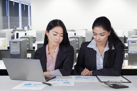 Two multiracial businesswomen looking at financial chart on the paperwork, shot in the office photo