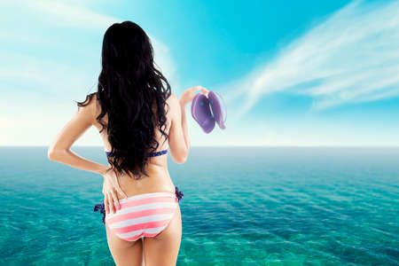 hot ass: Rear view of young woman standing on the coast while wearing swimwear and holding flip-flops