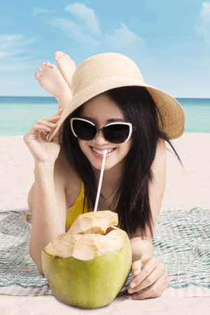 coconut drink: Attractive young woman smiling on the camera while drinking coconut water on the beach Stock Photo