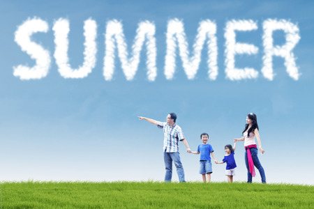Four member of happy asian family looking at something on the meadow under a summers cloud Stock Photo