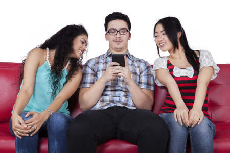 Caucasian man using mobile phone to send message near the curious friends photo