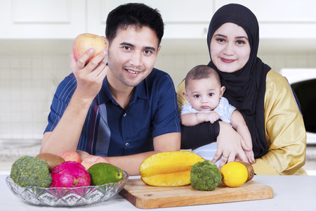 moslem: Portrait of healthy asian family smiling at the camera while sitting in the kitchen with fresh fruits Stock Photo