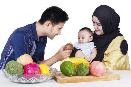 moslem: Portrait of happy father giving a fresh fruit to his little son, isolated on white background