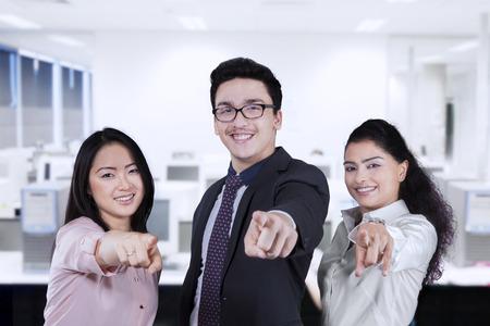 jonge ondernemers: Groep van jonge ondernemers lachend en wijzend naar de camera in de werkplaats Stockfoto
