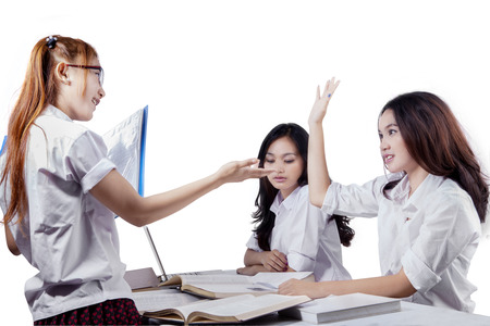 enquire: Female high scholl student raise hand and inquire a question on her friend Stock Photo