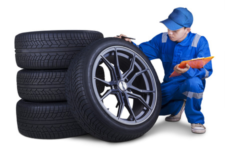 Male technician with a blue uniform, holding a clipboard while checking tires