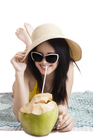 Joyful young woman lying on the mat while wearing swimsuit, hat, and sunglasses. enjoy coconut water, isolated on white photo