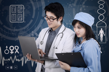 medical assistant: Young male doctor and medical assistant looking at computer Stock Photo
