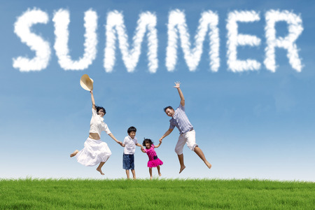 asian family outdoor: Joyful young asian family holding hands and jumping together on the green meadow under a summers cloud Stock Photo