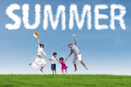 Radostné mladých asijských rodina drží za ruce a skákání společně na zelené louce pod letního oblaku