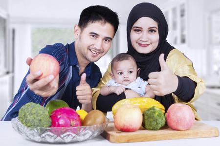 personas saludables: Familia sana que muestra el pulgar hacia arriba en la cocina con frutas frescas en la mesa