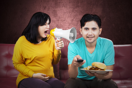 Emotion of angry pregnant woman yelling at her husband in the home photo