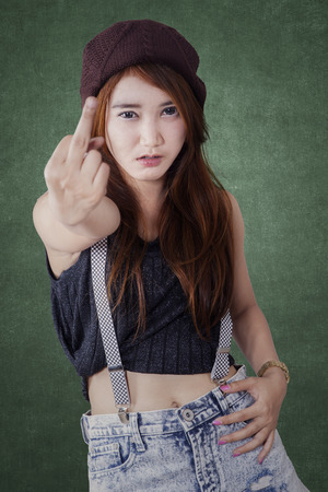 arrogant teen: Portrait of naughty girl with casual clothes showing middle finger gesture Stock Photo