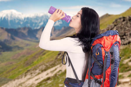mountainside: Attractive young backpacker drinking fresh water while carrying backpack for hiking on the mountainside