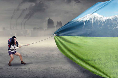 life change: Female hiker pulling a banner of friendly environment, symbolizing she try to save the environment Stock Photo