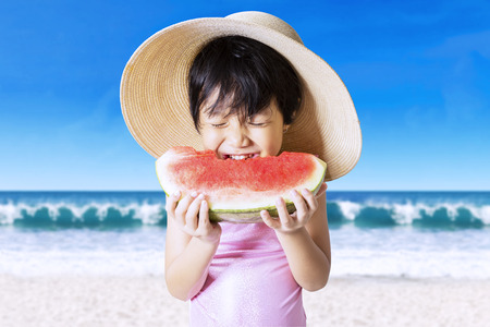 Portrait of cute little girl bites a watermelon on the beach while wearing a big hat and swimsuit