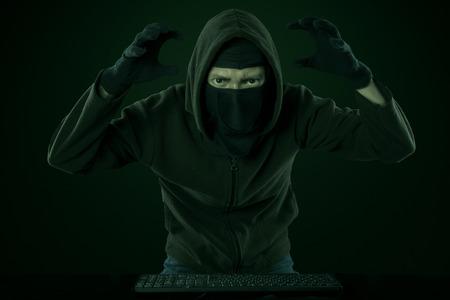 grabbing: Portrait of dangerous hacker posing for grabbing information