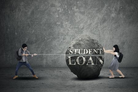 empujando: Concepto costoso costos de la educación con los estudiantes tirando y empujando la piedra pesada