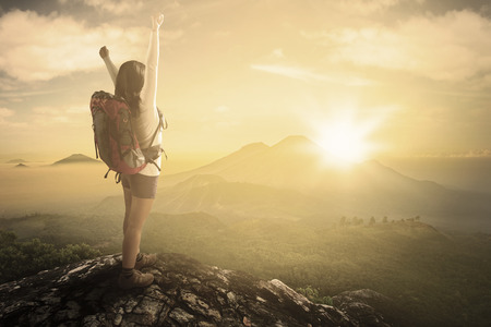 Back view of young woman standing on the cliff while enjoying her freedom and carrying backpack for hiking photo