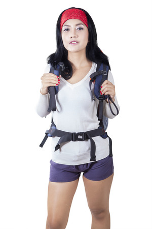 japanese woman: Portrait of beautiful woman standing in the studio while carrying backpack for hiking, isolated on white background Stock Photo