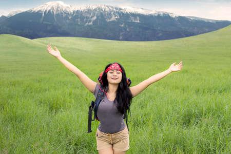 aire puro: Retrato de la hermosa mujer de senderismo en la montaña y disfrutar de aire fresco mientras estira sus manos
