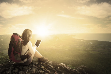 Rear view of female backpacker sitting on the mountain while using tablet and enjoying valley view