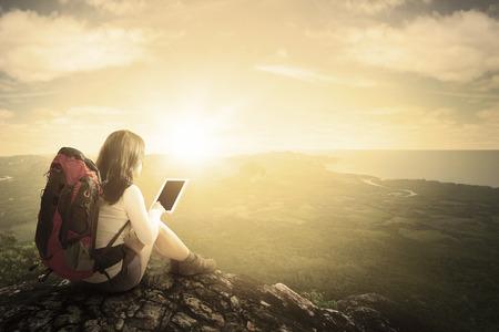 Vue arrière du routard femme assis sur la montagne tout en utilisant la tablette et profiter de vue sur la vallée