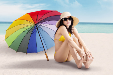 Beautiful young woman enjoy holiday while sitting on the shore with colorful umbrella and wearing swimsuit photo
